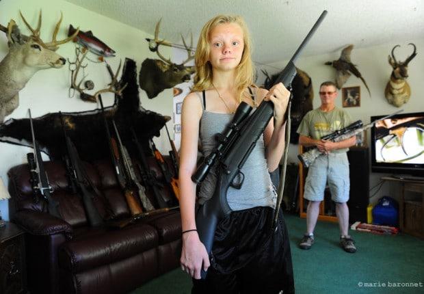 """Tim Earnhart et sa fille Aspen. Kearns Utah. Aspen a 13 ans. L'âge légal pour l'achat d'armes est 18 ans. Aspen tient un Remington 243. """"La chasse c'est un truc de famille"""" me dit elle. L'Utah est un des états ou l'on peut porter une arme au vu de tous. Tim défend la notion d'autodéfense et ne laisserait personne lui retirer ses armes. Sa grande phrase comme pour tous ces semblables: """" ce ne sont pas les fusils qui tuent, mais les gens qui se servent des fusils pout tuer""""."""