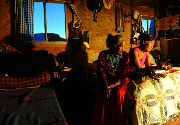 """Monument Valley Utah Arizona 2013. Mary  60 and her mother Helen 80, working on their jewelry that they sell to the tourists. They have no electricity or water. They supplement their income with the """"Hogan experience"""": one night without electricity and water for a 150 dollars."""