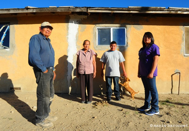 Blue Gap Arizona 2013. Jimmy his wife Candy and their children in front of their home. The crack is caused by unstable ground from over exploitation of the underground